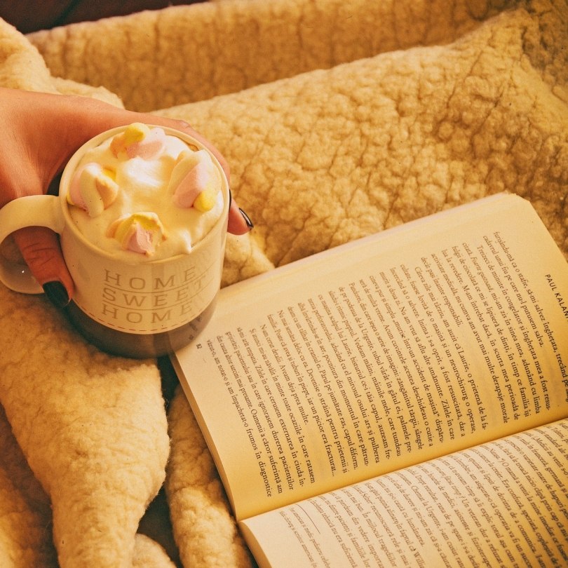 A hand holds a hot chocolate with marshmallows next to an open book.